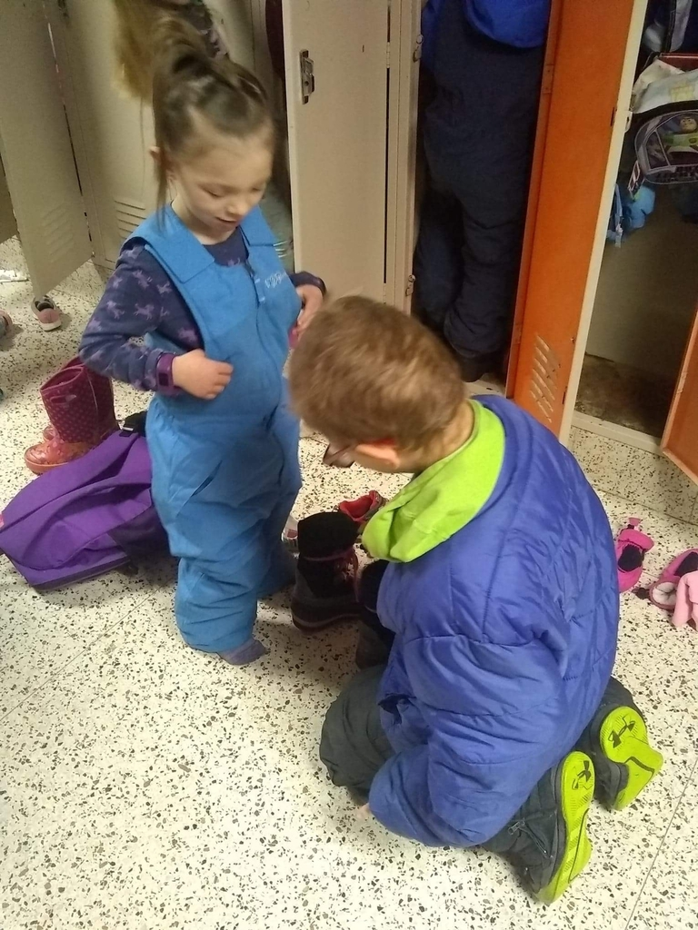 Big brother helps little sister get winter gear on!